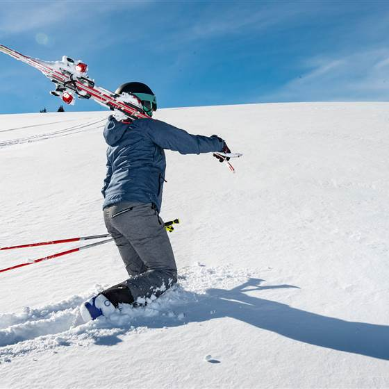 Frau trägt Skier auf Schulter im durch den Schnee