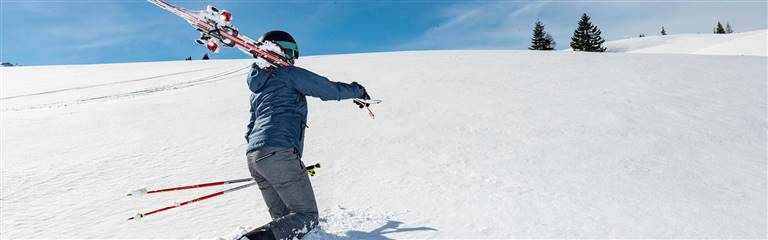 Man carries ski over his shoulder